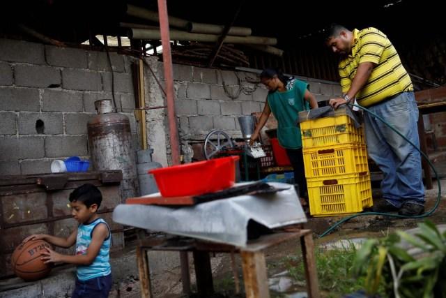 Medical equipment repairman Leandro Colmenares (R) makes corn dough at the backyard of his house in Caracas, Venezuela October 3, 2017. Picture taken October 3, 2017. REUTERS/Carlos Garcia Rawlins