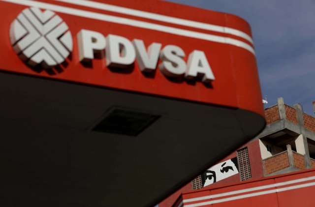 A painting depicting the eyes of Venezuela's late President Hugo Chavez, is pictured close to a corporate logo of the state oil company PDVSA at a gas station in Caracas, Venezuela, October 10, 2017. Picture taken October 10, 2017. REUTERS/Ricardo Moraes
