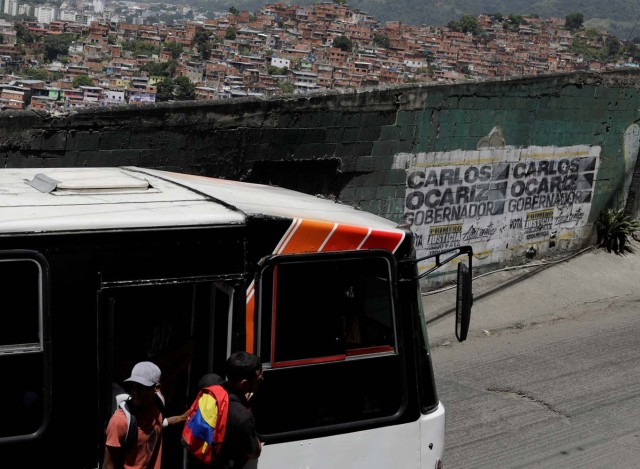 A public bus drive past a campaign graffiti of opposition candidate for the government of Miranda Carlos Ocariz ahead the governors elections, which will be held on October 15, in Caracas, Venezuela, October 13, 2017. REUTERS/Ricardo Moraes