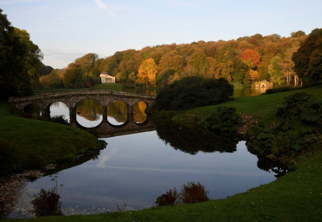 Autumn colours are seen in the early morning sunshine as a woman walks her dog at Stourhead gardens in Wiltshire, south west Britain, October 17, 2017. REUTERS/Toby Melville