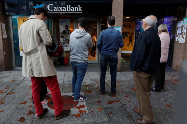 People line up at a cashpoint of La Caixa bank branch to withdraw money as part of an action to protest the transfer of the bank's headquarters out of Barcelona, Spain, October 20, 2017. REUTERS/Gonzalo Fuentes
