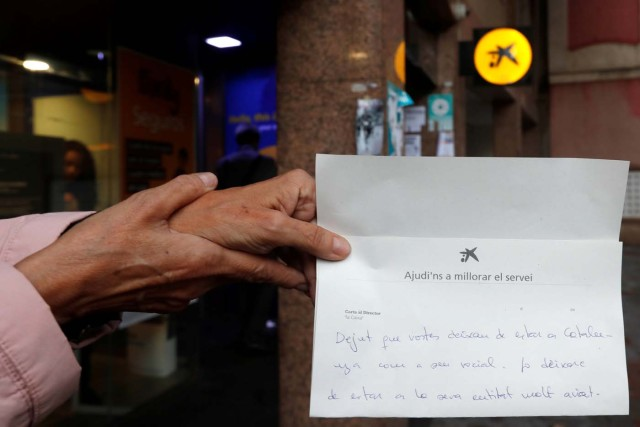 A woman shows a complaint letter addressed to La Caixa bank, to protest the transfer of the bank's headquarters out of Barcelona, Spain, October 20, 2017. REUTERS/Gonzalo Fuentes
