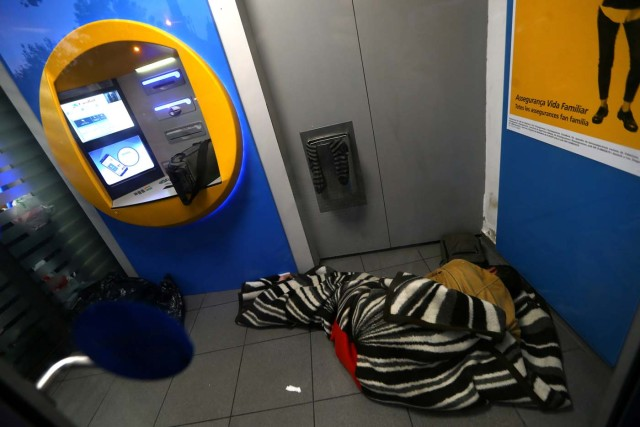 A man sleeps by a Caixa Bank ATM at their branch office, on the day of a protest against the transfer of the bank's headquarters out of Barcelona, Spain, October 20, 2017. REUTERS/Ivan Alvarado