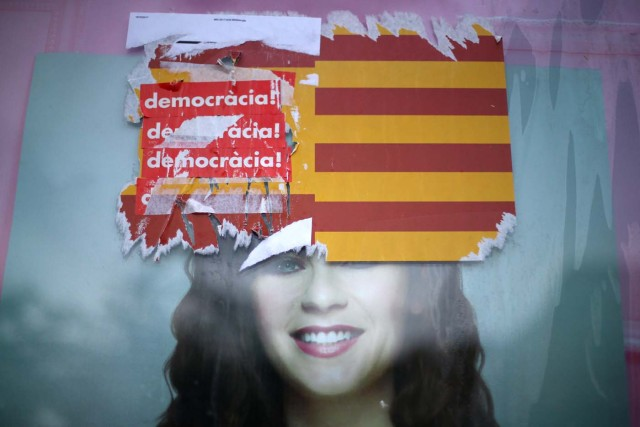 """Stickers reading """"Democracy!"""" are seen on Spanish and Catalan flags during the day of a protest against the transfer of the Sabadell and Caixa banks' headquarters out of Barcelona, Spain, October 20, 2017. REUTERS/Ivan Alvarado"""