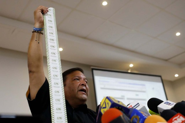 Andres Velasquez, former candidate for governor of Bolivar state, shows an electoral act as he talks to the media during a news conference in Caracas, Venezuela, October 20, 2017. REUTERS/Marco Bello