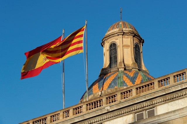 Las banderas españolas (L) y catalana ondean sobre el Palacio de la Generalitat, la sede del gobierno regional catalán en Barcelona, España, el 30 de octubre de 2017. REUTERS / Yves Herman