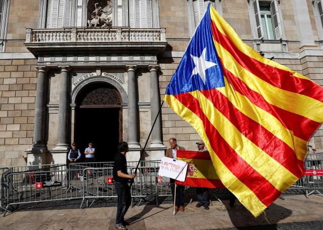 Un hombre con una bandera separatista catalana (L) mira a los hombres que sostienen una bandera española frente al Palacio de la Generalitat, la sede del gobierno regional de Cataluña en Barcelona, España, el 30 de octubre de 2017. REUTERS / Juan Medina