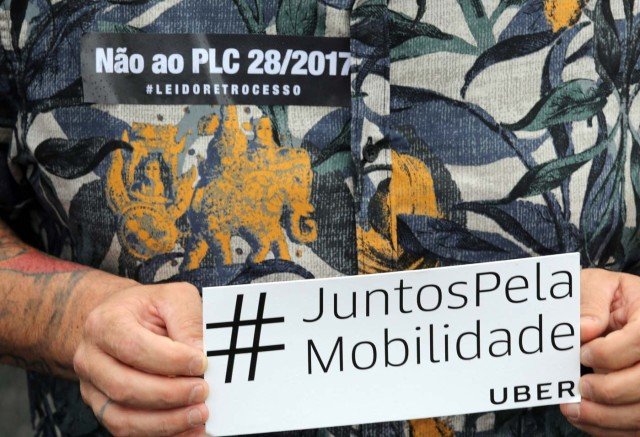 """An Uber driver holds a banner during a protest against a legislation threatening the company's business model that is to be voted in Brazil's national congress, in Sao Paulo, Brazil October 30, 2017. The banner reads """"#Together for mobility"""". REUTERS/Paulo Whitaker"""