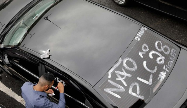 An Uber river paints his car during a protest against a legislation threatening the company's business model that is to be voted in Brazil's national congress, in Sao Paulo, Brazil October 30, 2017. REUTERS/Paulo Whitaker