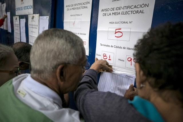 Varias personas asisten a un centro de votación hoy, 15 de octubre de 2017, en Caracas (Venezuela). Los centros de votación en Venezuela comenzaron hoy a abrir sus puertas a las seis de la mañana hora local (10.00 GMT), como estaba previsto, para atender a los ciudadanos que están llamados a participar en la elección de los 23 gobernadores del país caribeño. EFE/Miguel Gutiérrez