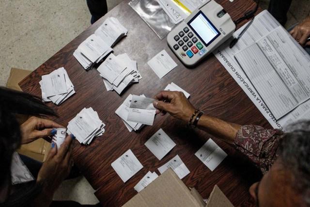 VEZ21. CARACAS (VENEZUELA), 15/10/2017.- Miembros de mesa y testigos participan en el cierre de mesas y auditoría de actas, en un centro electoral tras las elecciones regionales hoy, domingo 15 de octubre de 2017, en Caracas (Venezuela). Los venezolanos votaron hoy a un ritmo lento y sin grandes colas en muchos de los colegios durante la primera mitad de una jornada electoral de los comicios para elegir los gobernadores de 23 estados marcada por los retrasos en la apertura de las mesas. La oposición venezolana, reunida en la Mesa de la Unidad Democrática (MUD), pidió hoy que se cierren los centros donde ya no haya electores para iniciar conteo y exigió que se mantengan abiertos aquellos donde aún haya gente en fila para votar, pues resaltó que esto está establecido en la ley. EFE/Cristian Hernández