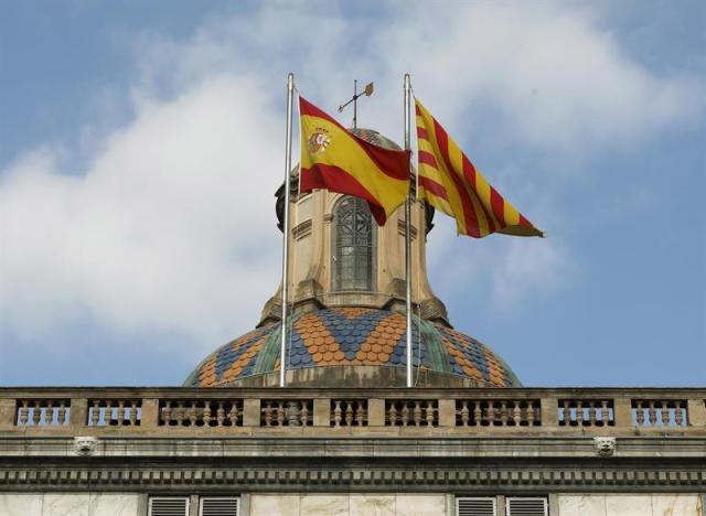 Las banderas española y catalana ondean ondean en la fachada del edificio de la Generalitat de Catalunya en la plaza de Sant Jaume tras la declaración unilateral de independencia ayer en el parlamento autonómico. EFE/ Andreu Dalmau