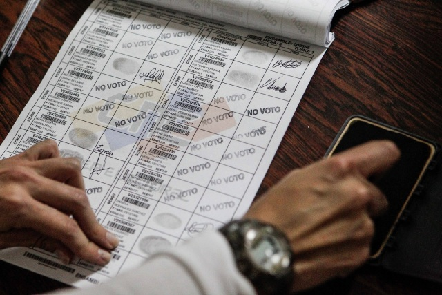 Un miembro de mesa marca con un sello a los electores que se abstuvieron en el cuaderno de votantes EFE/Cristian Hernández