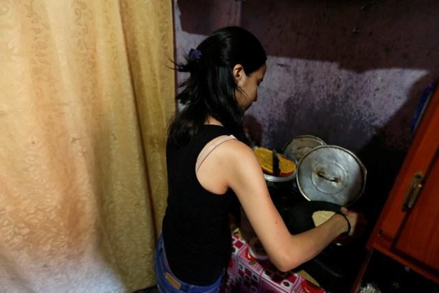 Yennifer Padrón cocina arepas en el cuarto familiar de la casa que comparten en el barrio pobre de Caracas, Venezuela, 21 de agosto de 2017. Foto tomada el 21 de agosto de 2017. Para coincidir con la característica VENEZUELA-NIÑOS / REUTERS / Andres Martinez Casares