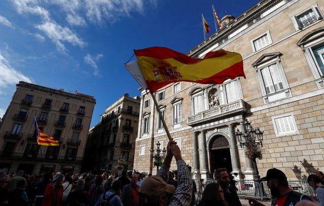 Spanish and Catalan separatist flags are waved in front of the Generalitat Palace, the Catalan regional government headquarters in Barcelona, Spain, October 30, 2017. REUTERS/Juan Medina