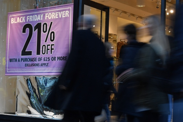 Shoppers pass a promotional sign for 'Black Friday' sales discounts on Oxford Street in London, on November 23, 2017. Black Friday is a sales offer originating from the US where retailers slash prices on the day after the Thanksgiving holiday. In the UK it is used as a marketing device to entice Christmas shoppers with the discounts at stores often lasting for a week. / AFP PHOTO / Ben STANSALL