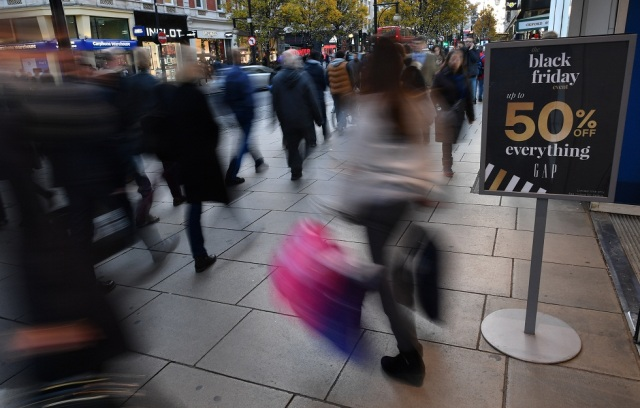 Shoppers pass a promotional sign for 'Black Friday' sales discounts as they exit a retail store on Oxford Street in London, on November 23, 2017. Black Friday is a sales offer originating from the US where retailers slash prices on the day after the Thanksgiving holiday. In the UK it is used as a marketing device to entice Christmas shoppers with the discounts at stores often lasting for a week. / AFP PHOTO / Ben STANSALL