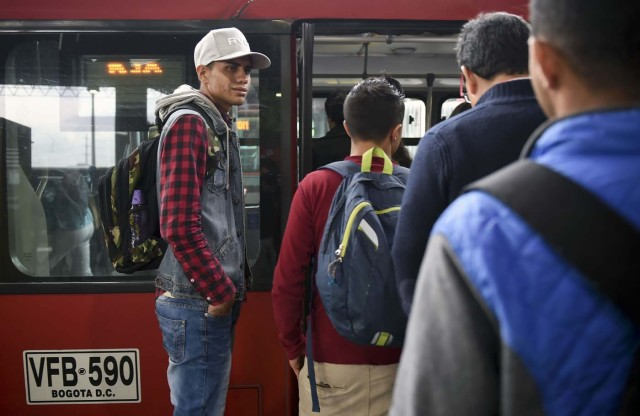 Venezuelan national Jhonger Pina, 25, awaits at a bus station in Bogota, before getting a bus to sell candies and show Bolivar bills as a curiosity to passengers in exchange for local coins, on October 26, 2017. Up to October 2017 there were 470,000 Venezuelans in Colombia, who left their country to escape the hardship and violence of its economic and political crisis. / AFP PHOTO / Raul Arboleda / TO GO WITH AFP STORY by Daniela QUINTERO and Santiago TORRADO