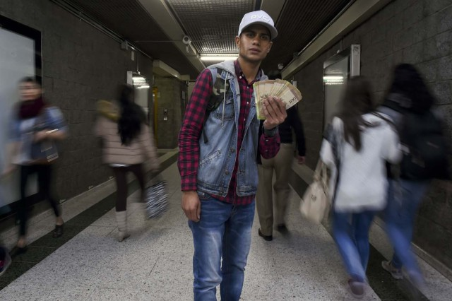 Venezuelan national Jhonger Pina, 25, shows Bolivar bills as a curiosity in exchange for local coins, at a bus station in Bogota, on October 26, 2017. Up to October 2017 there were 470,000 Venezuelans in Colombia, who left their country to escape the hardship and violence of its economic and political crisis. / AFP PHOTO / Raul Arboleda / TO GO WITH AFP STORY by Daniela QUINTERO and Santiago TORRADO