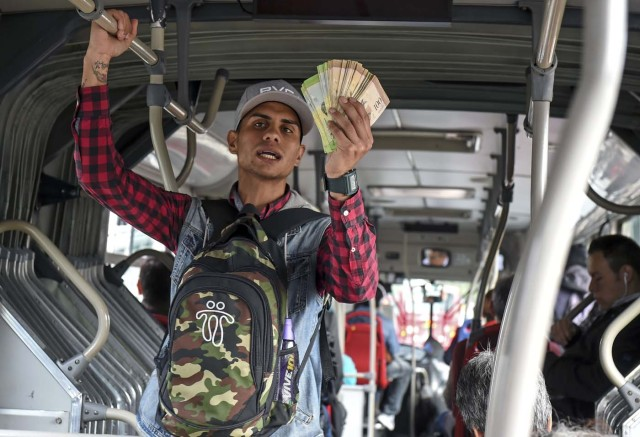Venezuelan national Jhonger Pina, 25, sells candies and shows Bolivar bills as a curiosity to passengers, in exchange for local coins on a bus in Bogota, on October 26, 2017. Up to October 2017 there were 470,000 Venezuelans in Colombia, who left their country to escape the hardship and violence of its economic and political crisis. / AFP PHOTO / Raul Arboleda / TO GO WITH AFP STORY by Daniela QUINTERO and Santiago TORRADO