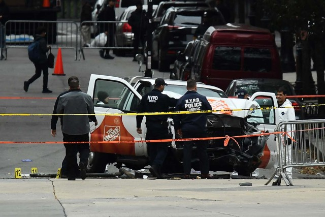 """Investigators work around the wreckage of a Home Depot pickup truck, a day after it was used in an terror attack, in New York on November 1, 2017. The pickup truck driver who plowed down a New York cycle path, killing eight people, in the city's worst attack since September 11, was associated with the Islamic State group but """"radicalized domestically,"""" the state's governor said Wednesday. The driver, identified as Uzbek national named Sayfullo Saipov was shot by police in the stomach at the end of the rampage, but he was expected to survive. / AFP PHOTO / Jewel SAMAD"""