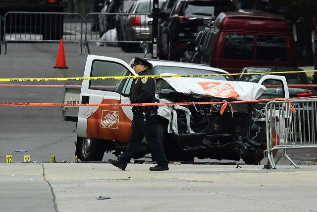 """A police officer walks past the wreckage of a Home Depot pickup truck, a day after it was used in an terror attack, in New York on November 1, 2017. The pickup truck driver who plowed down a New York cycle path, killing eight people, in the city's worst attack since September 11, was associated with the Islamic State group but """"radicalized domestically,"""" the state's governor said Wednesday. The driver, identified as Uzbek national named Sayfullo Saipov was shot by police in the stomach at the end of the rampage, but he was expected to survive. / AFP PHOTO / Jewel SAMAD"""