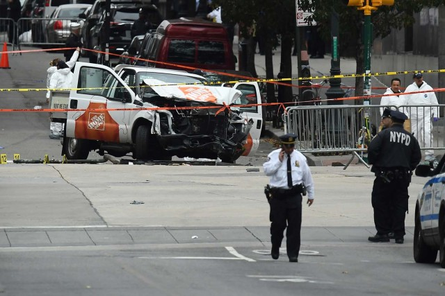 """Investigators work around the wreckage of a Home Depot pickup truck a day after it was used in a terror attack in New York on November 1, 2017. The pickup truck driver who plowed down a New York cycle path, killing eight people, in the city's worst attack since September 11, was associated with the Islamic State group but """"radicalized domestically,"""" the state's governor said Wednesday. The driver, identified as Uzbek national named Sayfullo Saipov was shot by police in the stomach at the end of the rampage, but he was expected to survive. / AFP PHOTO / Jewel SAMAD"""