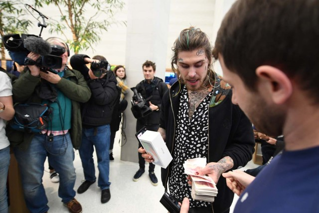 Marco White Jr., son of British chef Marco Pierre White pays cash for his Apple iPhone X after being the first to enter to buy the newly released smartphone at Apple's Regent Street store in central London on November 3, 2017. Apple's flagship iPhone X hit stores on November 3, as the world's most valuable company predicted bumper sales despite the handset's eye-watering price tag and celebrated a surge in profits. The device features facial recognition, cordless charging and an edge-to-edge screen made of organic light-emitting diodes used in high-end televisions. It marks the 10th anniversary of the first iPhone release and is released in about 50 markets around the world. / AFP PHOTO / CHRIS RATCLIFFE