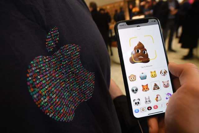 A member of Apple staff pose with a new Apple iPhone X smartphone showing new emoji features in Apple's Regent Street store in central London on November 3, 2017 after it opened for the first sales of the new smartphone. Apple's flagship iPhone X hit stores on November 3, as the world's most valuable company predicted bumper sales despite the handset's eye-watering price tag and celebrated a surge in profits. The device features facial recognition, cordless charging and an edge-to-edge screen made of organic light-emitting diodes used in high-end televisions. It marks the 10th anniversary of the first iPhone release and is released in about 50 markets around the world. / AFP PHOTO / Chris J Ratcliffe