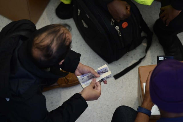 A customer holds a bundle of bank notes to pay for his Apple iPhone X after being one of the first to purchase the newly released smartphone at Apple's Regent Street store in central London on November 3, 2017. Apple's flagship iPhone X hit stores on November 3, as the world's most valuable company predicted bumper sales despite the handset's eye-watering price tag and celebrated a surge in profits. The device features facial recognition, cordless charging and an edge-to-edge screen made of organic light-emitting diodes used in high-end televisions. It marks the 10th anniversary of the first iPhone release and is released in about 50 markets around the world. / AFP PHOTO / CHRIS RATCLIFFE