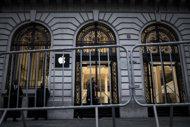 An Apple employee (C) walks past security personnels outside an Apple shop early morning on the release day of the new iPhone X in Paris on November 3, 2017. / AFP PHOTO / PHILIPPE LOPEZ