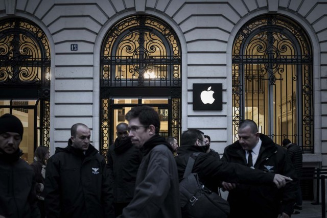 Apple employees stand outside an Apple shop early morning on the release day of the new iPhone X in Paris on November 3, 2017. / AFP PHOTO / PHILIPPE LOPEZ