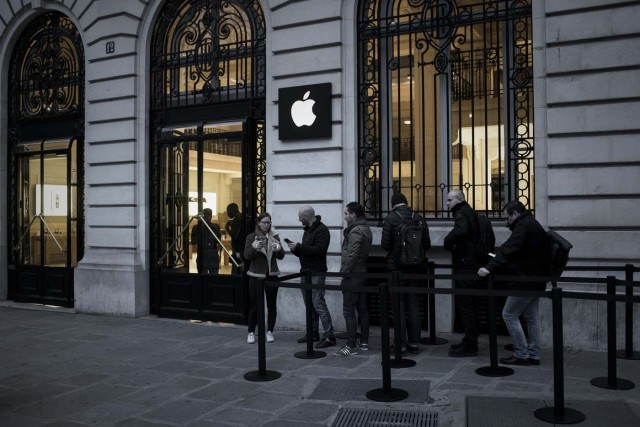 An Apple employee (L) chats with customers queuing to get their pre-ordered iPhones outside an Apple shop early morning on the release day of the new iPhone X in Paris on November 3, 2017. / AFP PHOTO / PHILIPPE LOPEZ