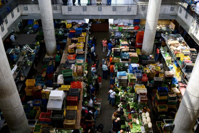People shop at the municipal market of Chacao in Caracas on November 2, 2017. This week, Venezuelan President Nicolas Maduro introduced a new bank note of 100,000 Bolivars - five times the current largest denomination - and announced a 30 percent minimum wage hike. / AFP PHOTO / FEDERICO PARRA