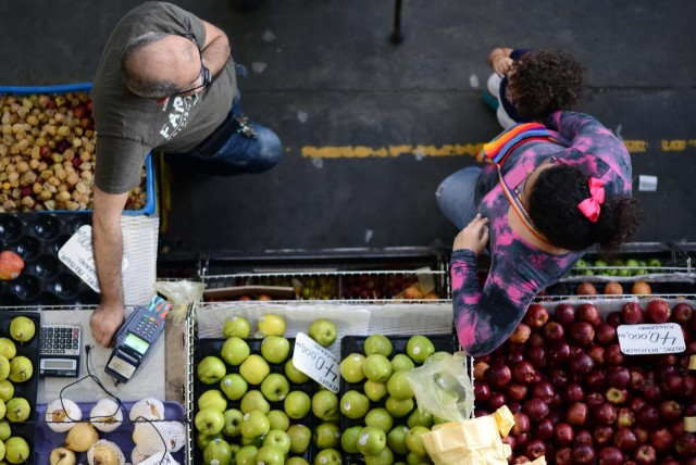 A fruits and vegetables seller waits for customers at the municipal market of Chacao in Caracas on November 2, 2017. This week, Venezuelan President Nicolas Maduro introduced a new bank note of 100,000 Bolivars - five times the current largest denomination - and announced a 30 percent minimum wage hike. / AFP PHOTO / FEDERICO PARRA