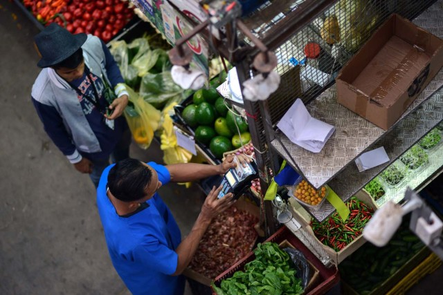 A man pays for groceries at the municipal market of Chacao in Caracas on November 2, 2017. This week, Venezuelan President Nicolas Maduro introduced a new bank note of 100,000 Bolivars - five times the current largest denomination - and announced a 30 percent minimum wage hike. / AFP PHOTO / FEDERICO PARRA
