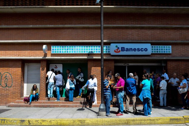 People queue to withdraw money from an ATM in Caracas on November 2, 2017. This week, Venezuelan President Nicolas Maduro introduced a new bank note of 100,000 Bolivars - five times the current largest denomination - and announced a 30 percent minimum wage hike. / AFP PHOTO / FEDERICO PARRA