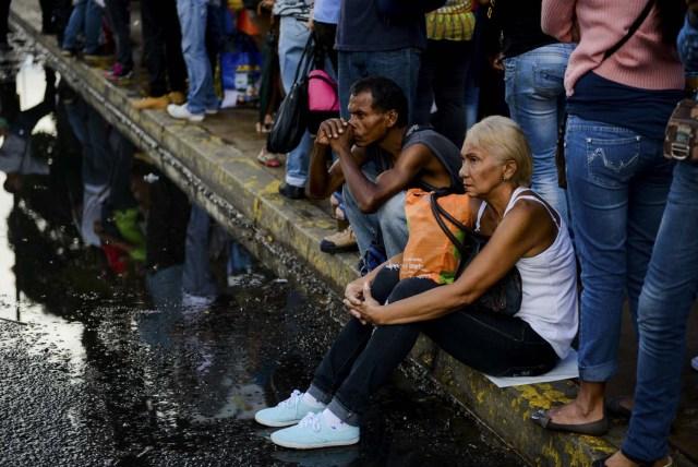Las personas hacen cola en una parada de autobús en Catia, un barrio de Caracas, el 1 de noviembre de 2017. La gente hace cola hasta cuatro horas para tomar un autobús a casa en Venezuela, donde la movilización por tierra o avión se ha convertido en un dolor de cabeza. / AFP PHOTO / Federico PARRA