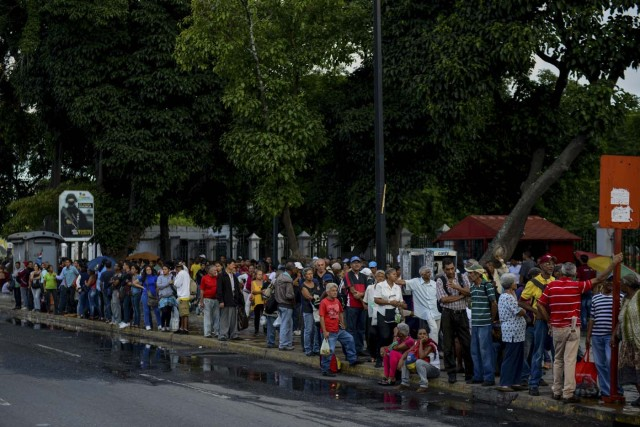 People queue at a bus stop in Catia, a neighbourhood of Caracas, on November 1, 2017. People queue for upto four hours to take a bus home in Venezuela, where mobilizing by land or plane has become a headache. / AFP PHOTO / Federico PARRA