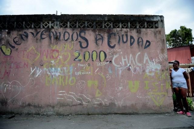 """Una mujer se encuentra junto a un muro que dice """"Bienvenido a Ciudad 2000"""" en City 2000, un barrio marginal que alberga a personas desplazadas por guerras territoriales entre bandas criminales en el municipio de Tumaco, departamento de Nariño, Colombia, el 2 de noviembre de 2017. En el remoto municipio de Tumaco, en la región costera del Pacífico colombiano, las pocas familias que no han huido viven con un temor constante a la violencia, a pesar del acuerdo de paz firmado en noviembre de 2016 entre el gobierno y los rebeldes de las FARC, debido a grupos armados que disputan la droga los corredores de tráfico a los Estados Unidos. / AFP PHOTO / Raul Arboleda"""