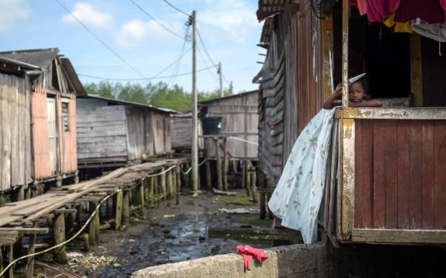 Un niño se encuentra en una casa en City 2000, un barrio de chabolas que alberga a personas desplazadas por guerras territoriales entre bandas criminales en el municipio de Tumaco, departamento de Nariño, Colombia, el 2 de noviembre de 2017. / AFP PHOTO / Raul Arboleda
