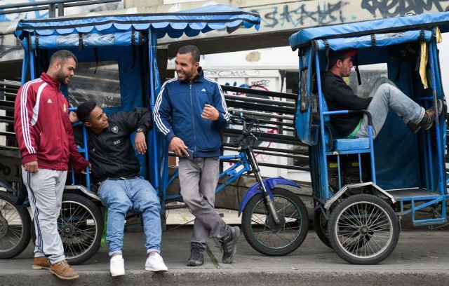"Venezuelan national Gregory Pacheco (3-L), 29, speaks with his compatriots before starting his working day as a ""bicitaxi"" (pedicab) driver in Bogota, on November 8, 2017. Up to October 2017 there were 470,000 Venezuelans in Colombia, who left their country to escape the hardship and violence of its economic and political crisis. / AFP PHOTO / Raul Arboleda / TO GO WITH AFP STORY by Daniela QUINTERO and Santiago TORRADO"