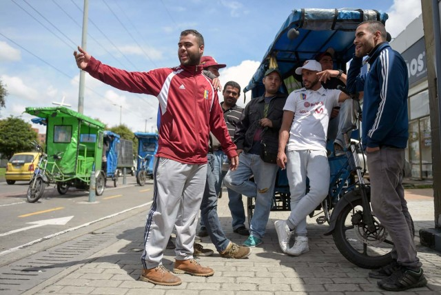 "Venezuelan national Gregory Pacheco (R), 29, speaks with his compatriots before starting his working day as a ""bicitaxi"" (pedicab) driver in Bogota, on November 8, 2017. Up to October 2017 there were 470,000 Venezuelans in Colombia, who left their country to escape the hardship and violence of its economic and political crisis. / AFP PHOTO / Raul Arboleda / TO GO WITH AFP STORY by Daniela QUINTERO and Santiago TORRADO"
