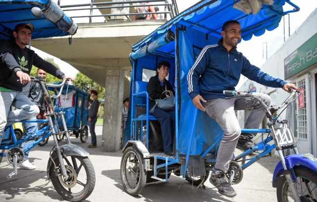 "Venezuelan national Gregory Pacheco (R), 29, works as a ""bicitaxi"" (pedicab) driver in Bogota, on November 8, 2017. Up to October 2017 there were 470,000 Venezuelans in Colombia, who left their country to escape the hardship and violence of its economic and political crisis. / AFP PHOTO / Raul Arboleda / TO GO WITH AFP STORY by Daniela QUINTERO and Santiago TORRADO"