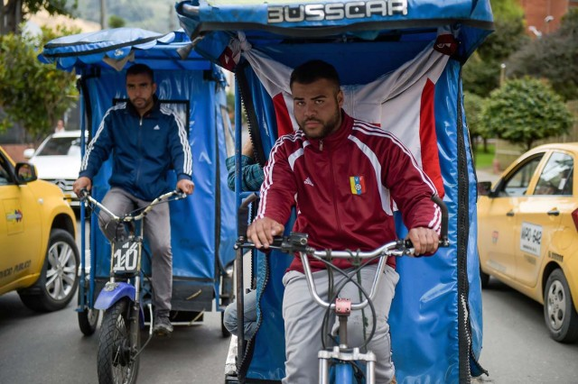 "Venezuelan national Gregory Pacheco (L), 29, works as a ""bicitaxi"" (pedicab) driver in Bogota, on November 8, 2017. Up to October 2017 there were 470,000 Venezuelans in Colombia, who left their country to escape the hardship and violence of its economic and political crisis. / AFP PHOTO / Raul Arboleda / TO GO WITH AFP STORY by Daniela QUINTERO and Santiago TORRADO"