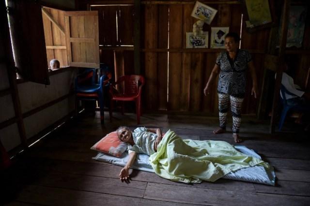 María Alegria (C), residente local de mayor edad, yace en una estera en el piso de su casa después de sufrir una mala caída, en Pital de la Costa, municipio de Tumaco, departamento de Nariño, Colombia el 31 de octubre de 2017. / Raul Arboleda