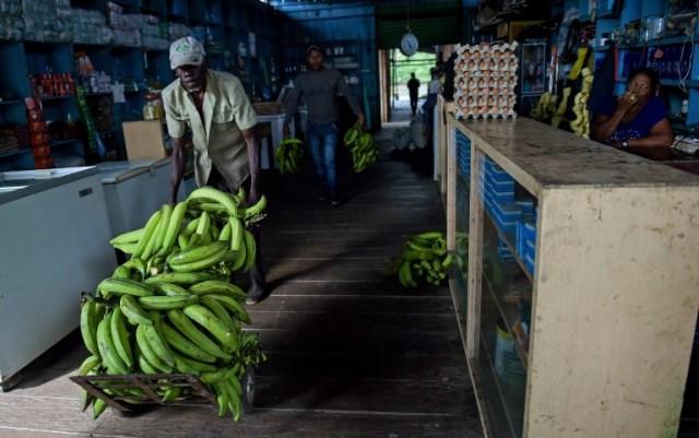Un residente local mueve una carga de plátanos en una tienda en Pital de la Costa, municipio de Tumaco, departamento de Nariño, Colombia, el 31 de octubre de 2017. En el remoto municipio de Tumaco, en la región costera del Pacífico colombiano, las pocas familias que no han huido viven con un temor constante a la violencia, a pesar del acuerdo de paz firmado en noviembre de 2016 entre el gobierno y los rebeldes de las FARC, debido a grupos armados que disputan la droga los corredores de tráfico a los Estados Unidos. / AFP PHOTO / Raul Arboleda