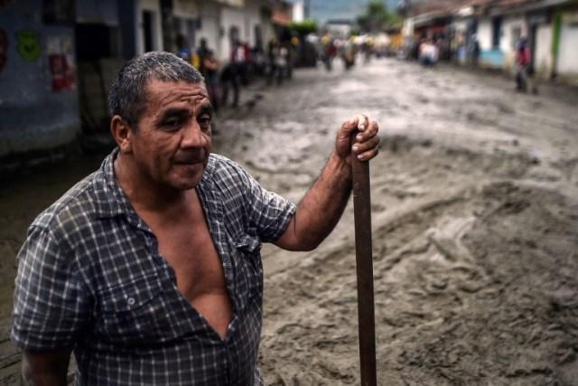 Un hombre se para en medio de una calle embarrada después de un alud debido a las fuertes lluvias que afectaron a Corinto en el departamento de Cauca, al suroeste de Colombia el 8 de noviembre de 2017. El deslizamiento de tierra afectó a Corinto el martes por la noche, dejando tres muertos, 32 heridos y 18 desaparecidos, además de cientos de viviendas afectadas, según el último balance proporcionado por las autoridades. / AFP PHOTO / LUIS ROBAYO