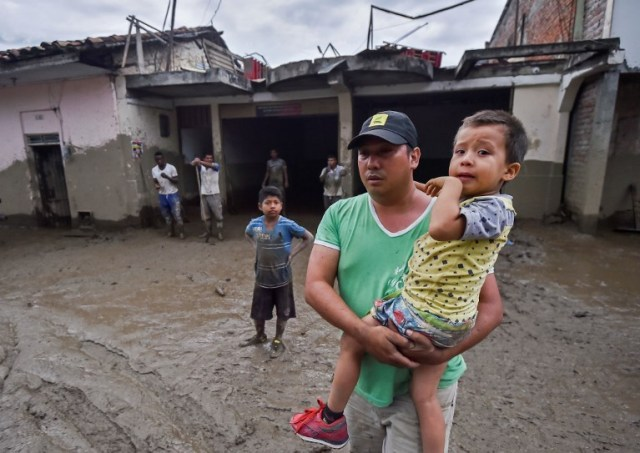 Un hombre sostiene a su hijo en medio de una calle fangosa, después de un alud debido a las fuertes lluvias que afectaron a Corinto en el departamento de Cauca, al suroeste de Colombia el 8 de noviembre de 2017. El deslizamiento de tierra afectó a Corinto el martes por la noche, dejando tres muertos, 32 heridos y 18 desaparecidos, además de cientos de viviendas afectadas, según el último balance proporcionado por las autoridades. / AFP PHOTO / LUIS ROBAYO