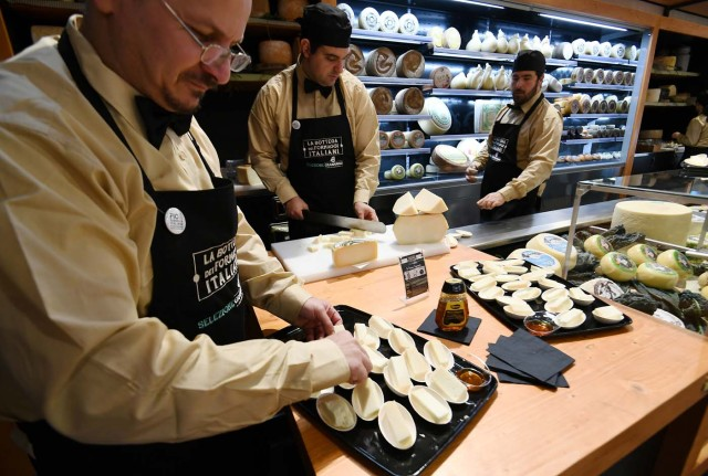 Vendors present different types of cheese at a stand during a press tour at FICO Eataly World agri-food park in Bologna on November 9, 2017. FICO Eataly World, said to be the world's biggest agri-food park, will open to the public on November 15, 2017. The free entry park, widely described as the Disney World of Italian food, is ten hectares big and will enshrine all the Italian food biodiversity. / AFP PHOTO / Vincenzo PINTO